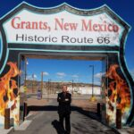 Gabe, qualifying broker for Doorway Dreams LLC real estate services standing by Grants, NM Route 66 sign